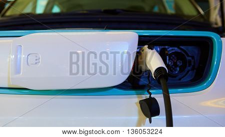 Charging an electric car with the power cable supply plugged in.