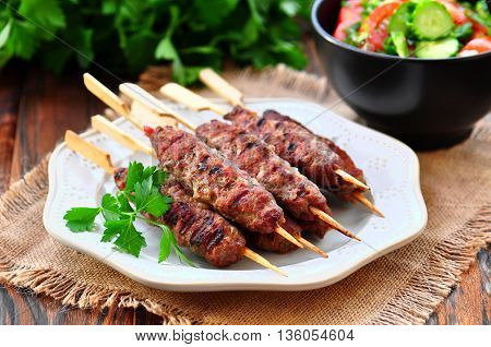 Homemade kebabs on skewers with a salad of tomato and cucumber.