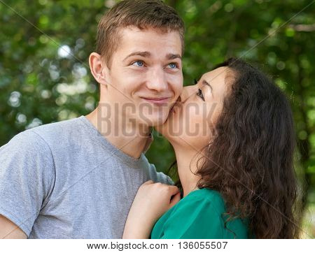 Romantic couple portrait posing in city park, girl kissing a guy, happy emotion, summer season, lovers boy and girl