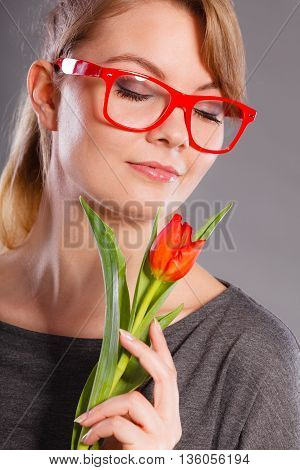 Peace and content. Beauty adorable girl smelling beautiful spring flower. Peaceful enjoyable woman with red green tulip. Lady smell nature.