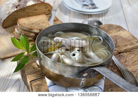 A Bavarian especially a Franconian specialty: Famous Nuremberg sausages  simmered in water with wine vinegar, onion rings and various spices like juniper berries and bay leaves