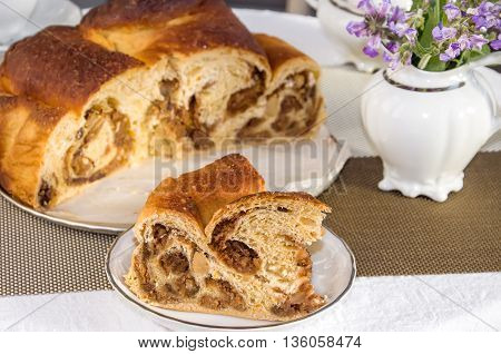 Good piece of typical italian flavorous home baked cake La Gubana with sophisticated stuffing (hazelnuts fruit chocolate walnut raisins honey etc.) with purple flowers of salvia. Traditionally bake for Christmas and Easter.