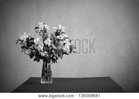 Bunch of blooming twigs on a table in monochrome. Retouched image. Vignette is added.
