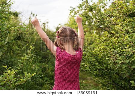 Little girl standing backward to the camera with her hands raised up on a summer day.