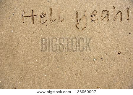 The words Hell Yeah written on sand