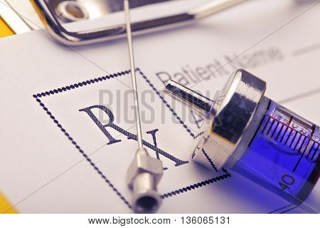 Vintage syringe on the background of RX blank.
