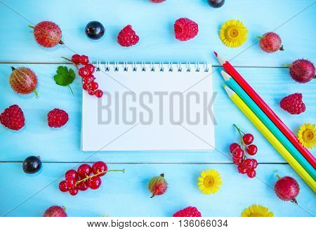 Ripe juicy summer berries black and red currant, gooseberry, raspberry,  green leave, yellow chamomiles  and blank notepad with colorful pencils on painted blue wooden background, space for text, recipe or message