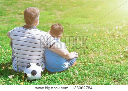 Cheerful old man and his grandson are sitting on grass near a ball in park. Grandparent is embracing a boy with love. Focus on their back. Copy space in right side