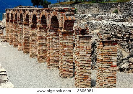 Sirmione Italy - June 1 2006: Ruins of the Roman villa which belonged to the poet Catullus at the Grottoes of Catallus overlook Lake Garda