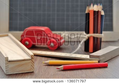 colored pencils on a slate with box rule and toy on a wooden background
