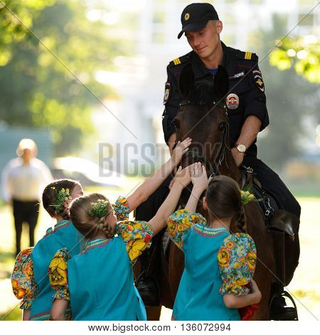 Orel Russia - June 24 2016: Turgenev Fest. Young Russian policeman on horse and little girls stroking it sqare