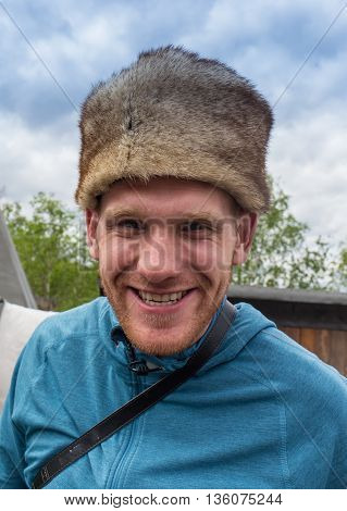 Winter portrait of happy young man smiling in hat.