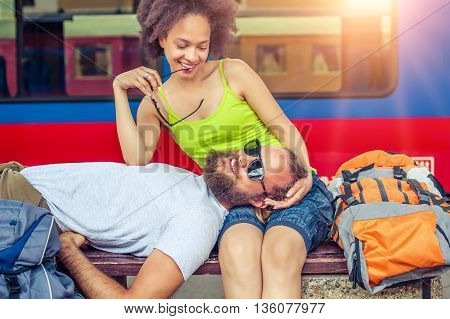 Beautiful couple backpacker tourist napping on a bench