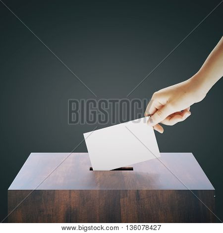 Hand with blank ballet casting vote into wooden ballot box on dark grey background. Voting concept. Mock up 3D Rendering