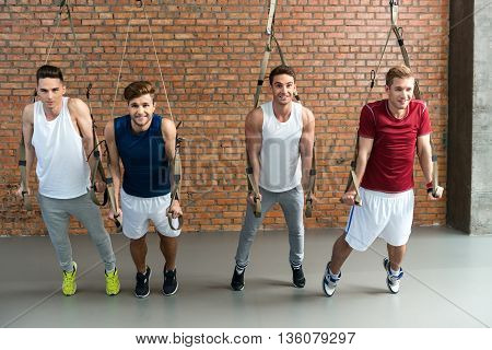 Great trx workout. Four fit sportsmen are doing push-ups while leaning on straps. They are looking at camera and smiling