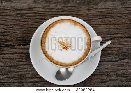 Hot cappuccino coffee cup on wooden table on brown background