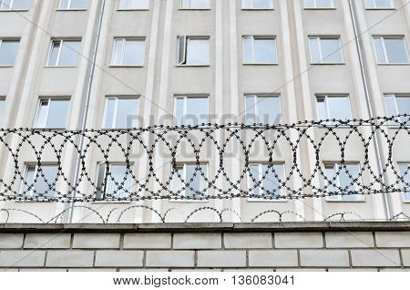 Gray building is fenced with barbed wire. Symbol of dictatorial and authoritarian regime. Limitation limitation of freedom and human rights.