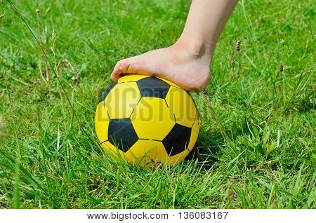 Children's Shoeless Foot And A Soccer Ball On Green Grass.
