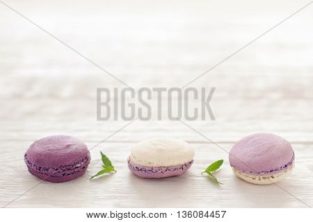 French purple macaroons horizontal line copyspace. Sweet macaroons put in hirizontal line in downside of pictire on white wooden background. Macaroons line decoratrd with mint