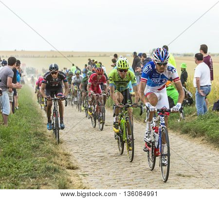 Quievy, France - July 07 2015: The peloton riding on a cobblestone road during the stage 4 of Le Tour de France 2015 in Quievy France on 07 July2015.