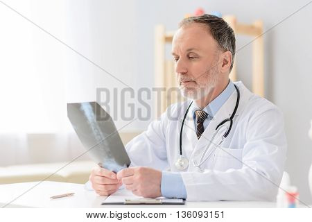 Taking closer look at problem. Portrait of smiling male doctor examining x-ray in his cabinet