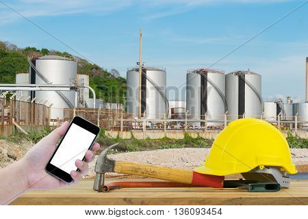Front view of Hand holding the black smartphone and Yellow Safety Helmet, Hammer, Cutting tools on Oil refinery industry with blue sky background