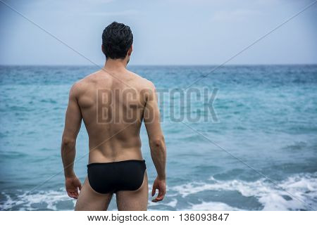 Back view of sexy unrecognizable man in trunks on beach against of sea