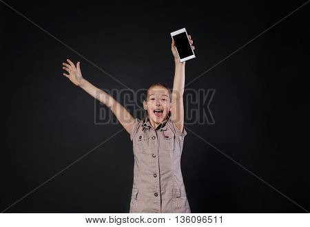 Happy cute little girl holding smartphone in hand, got device as a present. Child fascinated and excited, shouting hooray. Studio shot at black background poster