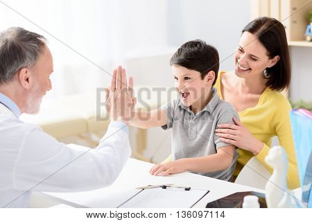 You are healthy little boy. Smiling boy giving high five to handsome middle aged doctor