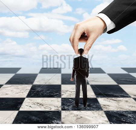 Big hand using tiny businessman as a pawn on chessboard. Sky background. Concept of control