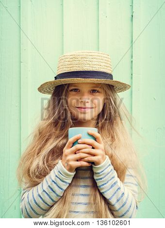 Cute little girl stands near a turquoise wall in boater hat and holding cup. Space for text.Negative speace