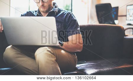 Successful Stockbroker working Laptop modern Interior Design Loft Office.Man work Vintage Sofa, Use contemporary Notebook, Browsing Internet.Blurred Background.Business Startup Idea Process.Horizontal.