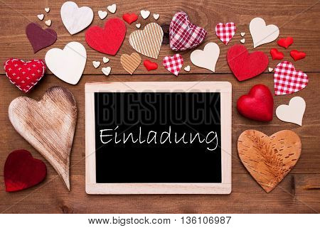 Chalkboard With German Text Einladung Means Invitation. Many Red Textile Hearts. Wooden Background With Vintage, Rustic Or Retro Style.