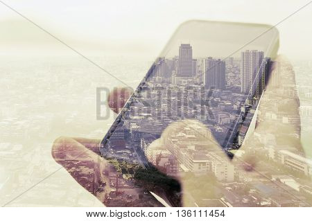 Double exposure image of businessman using smart phone with cityscape background