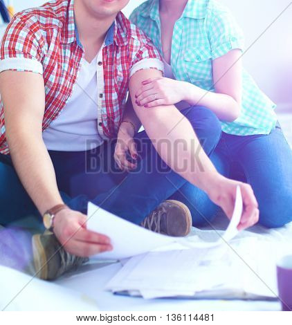 Young couple sitting on floor with apartment plan