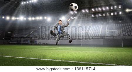 Businessman kicking ball . Mixed media