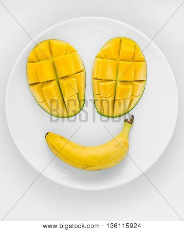 A smily face made from tropical fruit two mangoes and a banana on a white plate with white background.