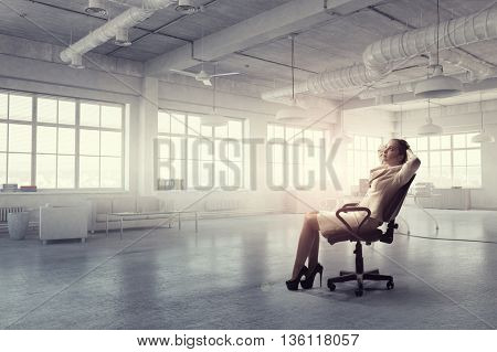 Businesswoman having rest in office . Mixed media