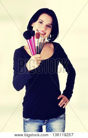 Make-up artist holding brushes