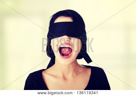 Frighten young blindfold woman screaming