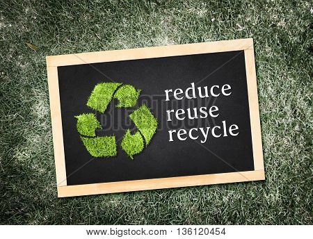 "Top view of recycle symbol and ""reduce reuse recycle"" word on blackboard with desaturated green grass background Eco concept. poster"