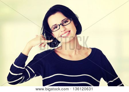 "Young woman gesturing ""call me"""