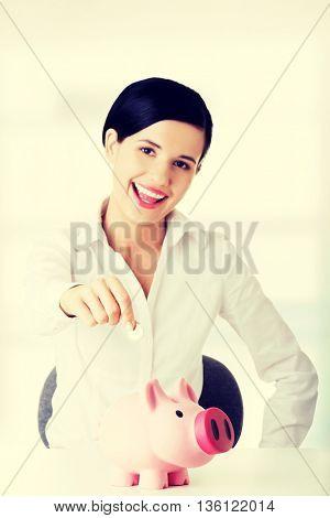 Businesswoman putting a coin into a piggy bank