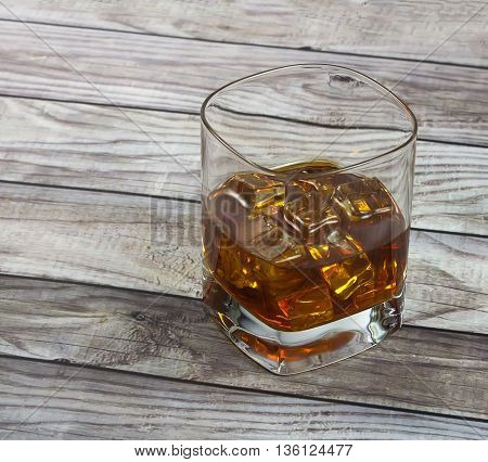 Closeup of a glass of whisky with ice cubes on reclaimed wood background