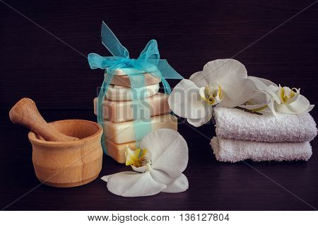 Spa and wellness setting with natural soap flowers wooden pounder and towels. Spa still life in white and blue colors on dark wooden background. Selective focus.