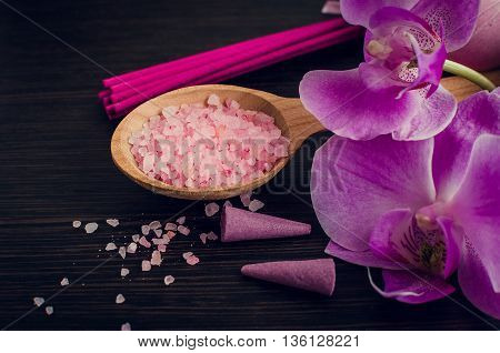 Spa and wellness still life with sea salt orchid and aromatic incense sticks in purple pink and violet colors on dark wooden background. Aromatherapy concept. Selective focus.