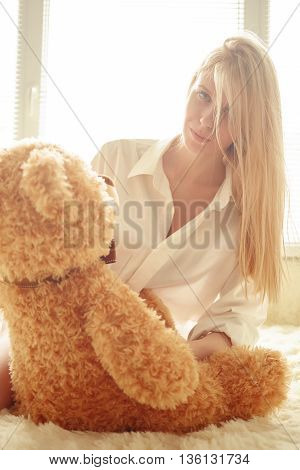 sad girl sitting with teddy bear in sun light toned image