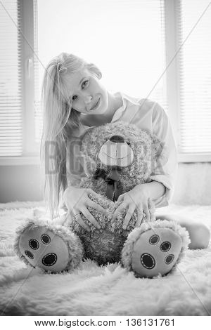 happy girl sitting with teddy bear in sun light monochrome image