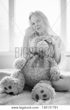 happy girl playing with teddy bear in sun light monochrome image