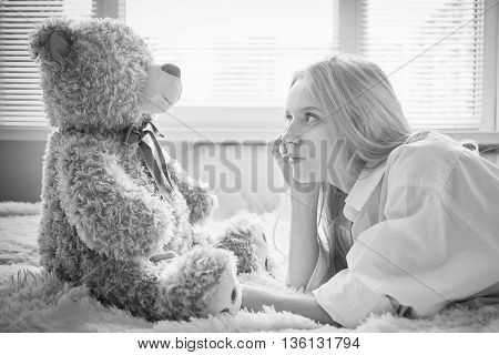 happy girl lying with teddy bear in sun light monochrome image